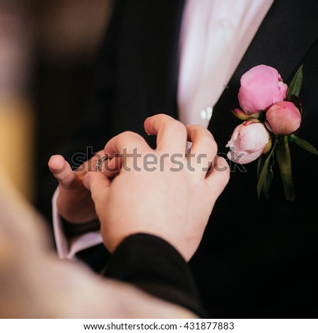 Happy spiritual bride & groom exchanging wedding rings in church b&w - stock photo