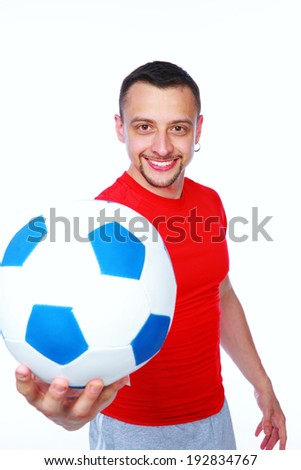 Happy sportive man holding soccer ball over white background - stock photo
