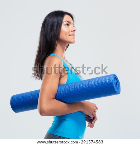 Happy sports woman holding yoga mat over gray background. Looking up - stock photo