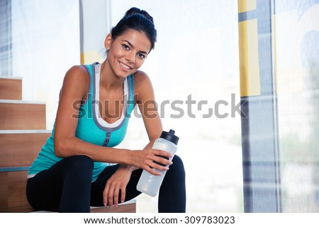 Happy sports woman resting on the stairs in gym with bottle of water - stock photo