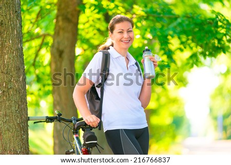 Happy sportswoman with a bottle of water and a bicycle - stock photo