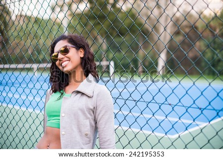 Happy sporty brunette woman near tennis court - stock photo