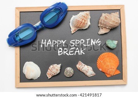 Happy Spring Break text on chalk board with swimming goggle and shell - vacation and business concept - stock photo