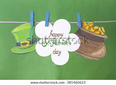 happy St Patrick's Day card, March 17, with Leprechaun hat and pot of gold, on pegs ( clothespin ) green background - stock photo