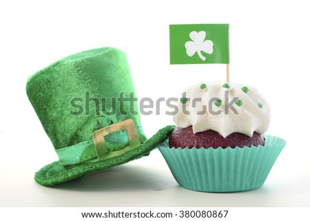 Happy St Patricks Day cupcake closeup with shamrock flags and green leprechaun hat on a white wood table.  - stock photo