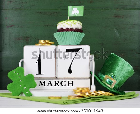Happy St Patricks Day save the date white vintage wood calendar with cupcakes on vintage style green wood background. - stock photo