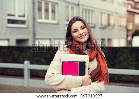 Happy student. Closeup portrait headshot professional beautiful confident young girl business woman holding books isolated cityscape outdoor background. Multicultural mixt race asian russian model - stock photo