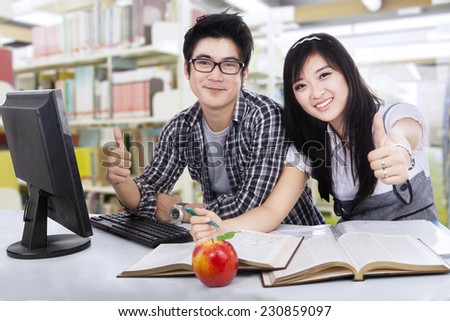 Happy student couple showing thumbs-up with computer on the desk - stock photo