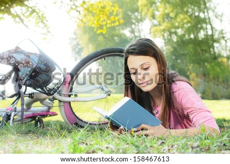 Happy student girl relaxing on green grass reading book.Bicycle in the background. - stock photo