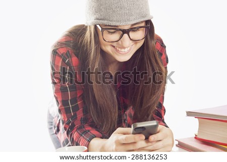 Happy student girl sending text message with mobile phone - stock photo