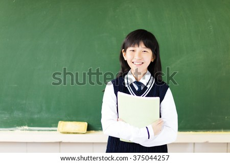 happy student girl with book in classroom - stock photo