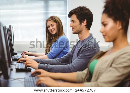 Happy student in computer class smiling at camera at the university - stock photo