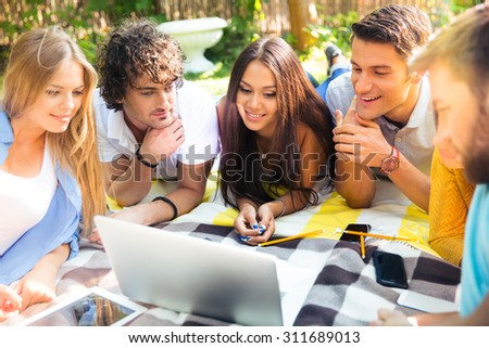 Happy student lying on plaid and looking at laptop outdoors - stock photo