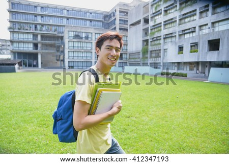 happy student on a grass at a campus - stock photo