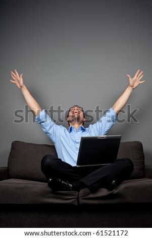 Happy student on lounge with hands raised sitting with laptop - stock photo
