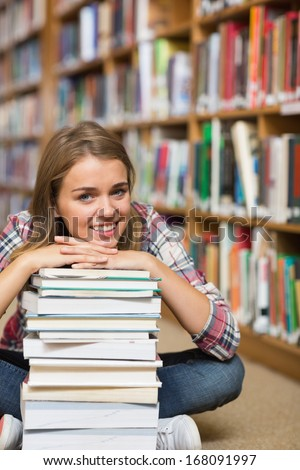 Happy student sitting on library floor leaning on pile of books in college - stock photo