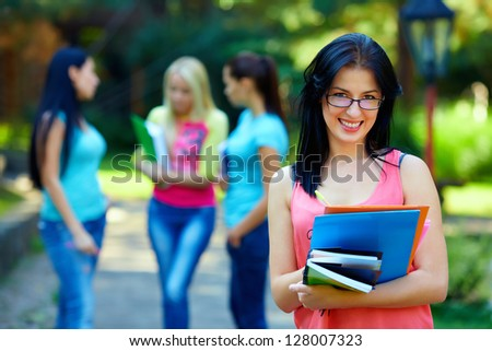 happy student wearing eyeglasses, colorful outdoors - stock photo