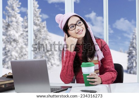 Happy student wearing sweater and dreaming something while studying and enjoy hot coffee at home - stock photo