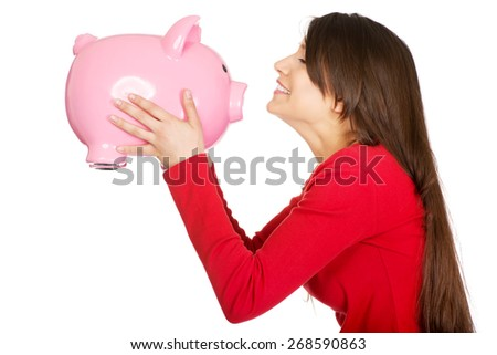 Happy student woman kissing her piggy bank. - stock photo