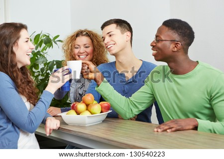 Happy students drinking coffee together in a cafe - stock photo