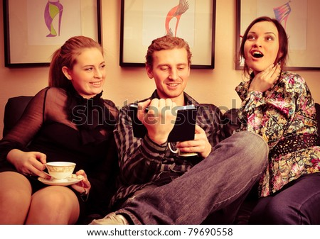 Happy students group demonstrating relaxation and friendship. Sitting on comfortable couch and writing their ideas on notepad - stock photo