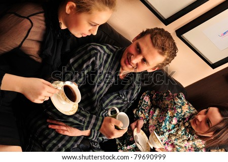 Happy students group demonstrating relaxation and friendship. Sitting on comfortable couch and drinking tea and coffee - stock photo