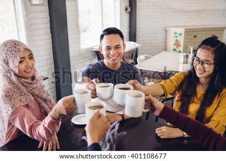 happy students having a cup of coffee chatting in college canteen - stock photo