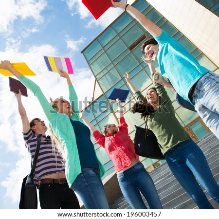 Happy students jumping for joy after the exam - stock photo