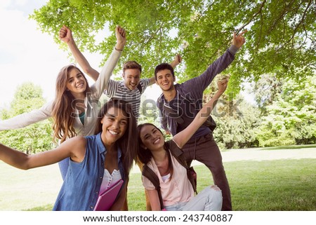 Happy students posing and smiling outside at the university - stock photo