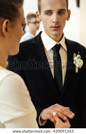 happy stylish bride and elegant groom exchanging wedding rings at ceremony at church - stock photo