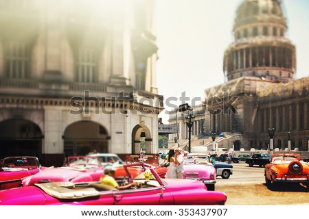 Happy stylish couple kissing in old city with old cars - stock photo