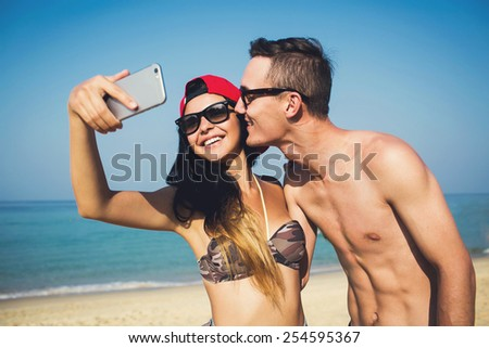 Happy stylish multiracial couple on honeymoon travel in Phuket beach coast, Thailand, taking selfie portrait photo with smartphone camera. - stock photo