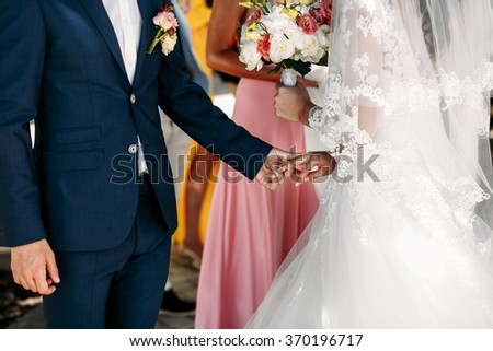 Happy stylish newlyweds in the ortodox church at wedding, creating new family - stock photo