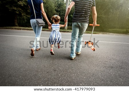happy stylish parents holding hands with daughter and walking in sunny  street, tender family moment - stock photo