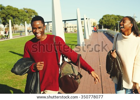 Happy stylish two dark skinned man and woman best friends having a great time together during their weekend, African couple smiling each to other while walking outdoors in beautiful sunny autumn day  - stock photo