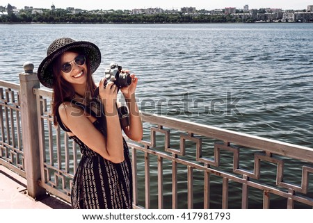 happy stylish woman hipster holding photo camera and smiling at sunny shore near water, summer travel concept, space for text - stock photo