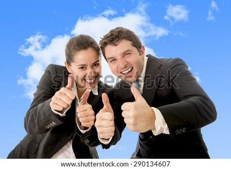 happy successful business Hispanic woman and Caucasian man wearing suits giving thumbs up smiling on blue sky background in career success concept - stock photo