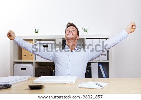 Happy successful business man cheering with clenched fists in office - stock photo