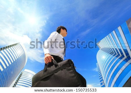 happy successful business man outdoors Next to Office Buildings with cityscape and sky in the background, asian people - stock photo