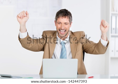 Happy successful businessman with clenched fists celebrating victory at office desk - stock photo