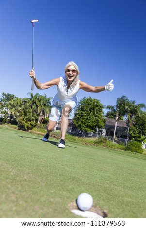 Happy successful senior woman playing golf putting a golf ball into a hole on a green and celebrating her success - stock photo