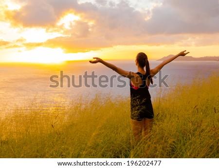 Happy successful sportswoman raising arms to the sky.  - stock photo