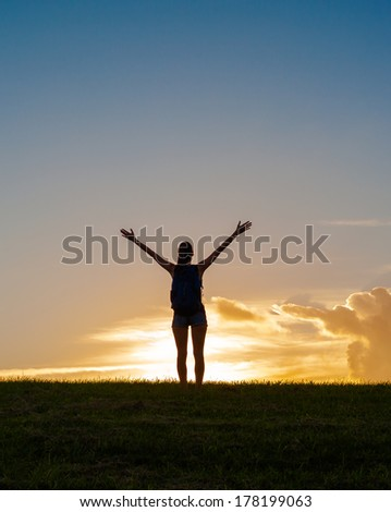 Happy successful woman with arms up celebrating to reach the mountain top. - stock photo