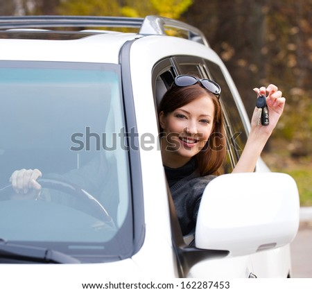 Happy successful woman with keys from the new car - outdoors  - stock photo