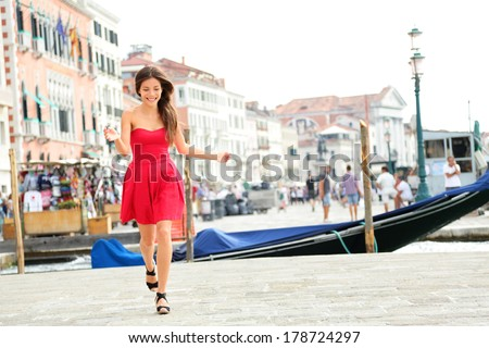 Happy summer girl running in dress in Venice, Italy. Woman smiling laughing joyful having fun by water in Venice. Beautiful multiracial Asian Caucasian young woman in full body length. - stock photo