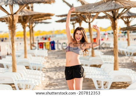 Happy sunshine woman. Girl smiling friendly looking at camera on sunny summer day under the hot sun on beach.  - stock photo
