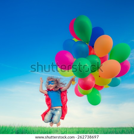 Happy superhero child jumping with colorful toy balloons outdoors. Smiling kid having fun in green spring field against blue sky background. Freedom concept - stock photo