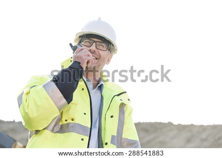 Happy supervisor using walkie-talkie at construction site against clear sky - stock photo