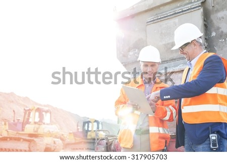 Happy supervisors discussing over clipboard at construction site against clear sky - stock photo