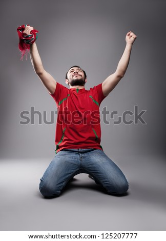 happy supporter with his hands up posing - stock photo